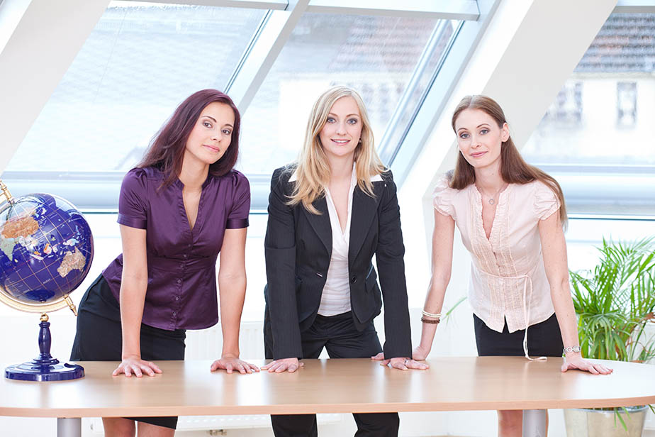 three girls in business outfit looking serious