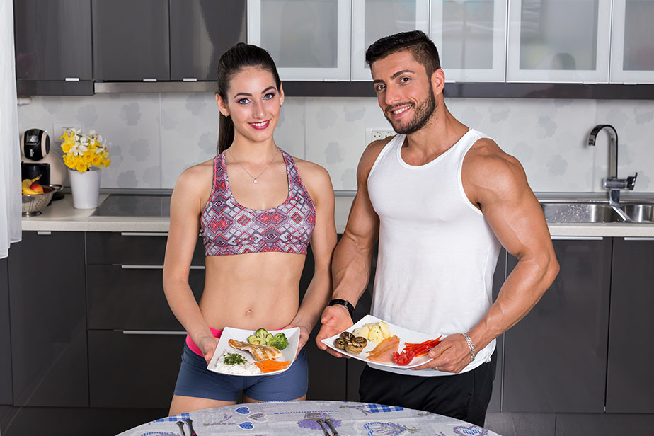 fit couple in the kitchen, holding plates of healthy food: rice, chicken grill, broccoli, carrots, mushrooms, potatoes, salmon, tomato, red peppers