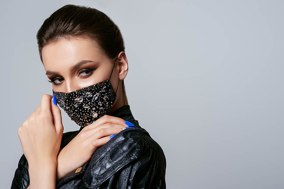 Woman wearing stylish protective black velvet face mask with silver rhinestones, beads. Fashion accessory during quarantine of coronavirus. Close up studio portrait. Copy, empty space for text